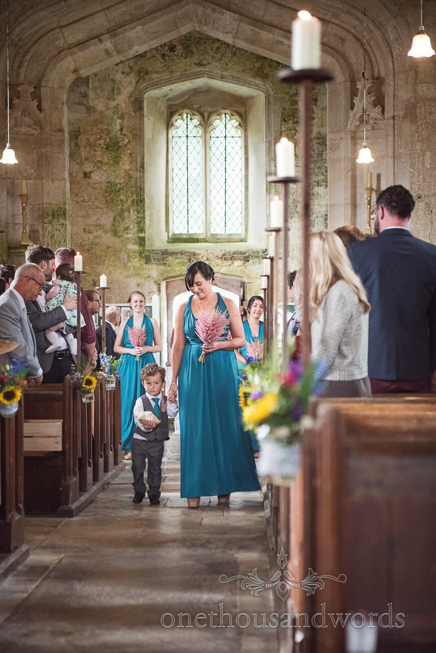 Page boy and bridesmaid lead bridal party into church at Lulworth Castle Wedding Photographs
