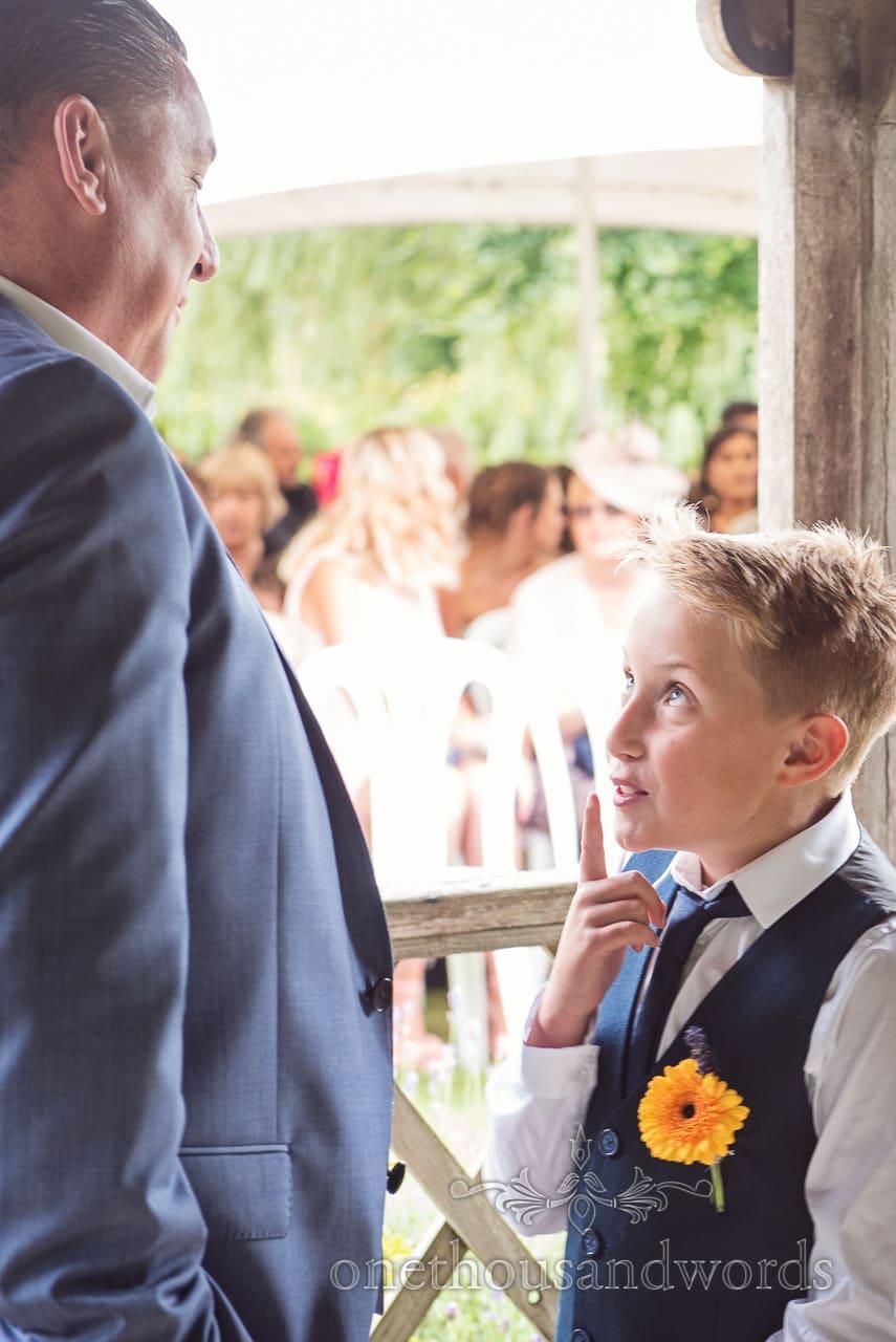 Page boy tells best man to be quiet at Morten Walled Gardens Wedding photograph
