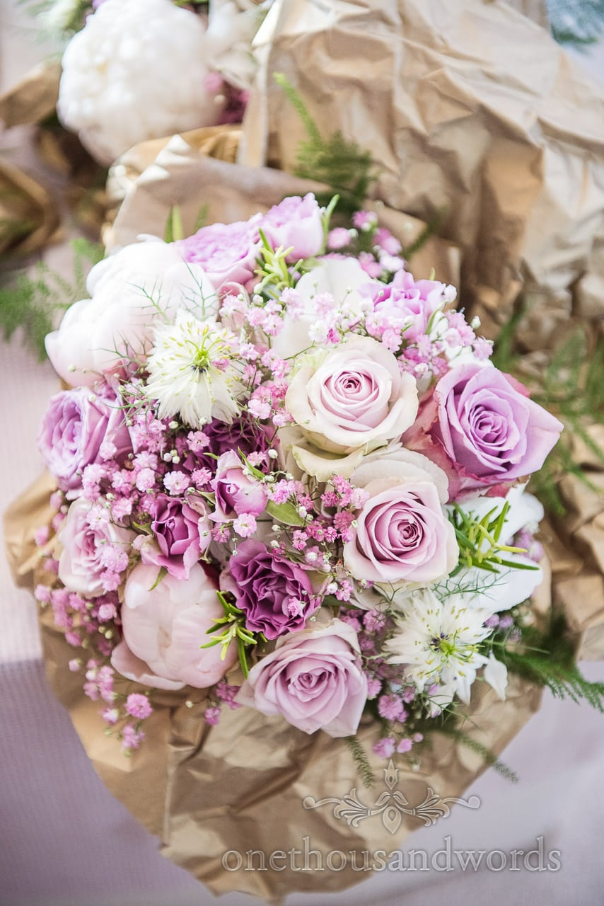 Purple and white wedding flowers bouquet with rosemary and green foliage