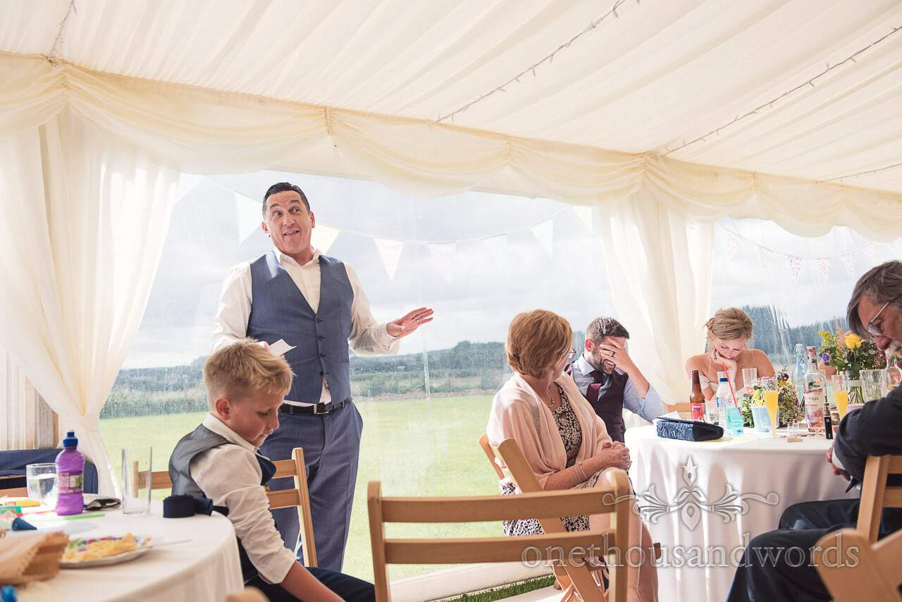 Reaction to best man speech during marquee wedding reception