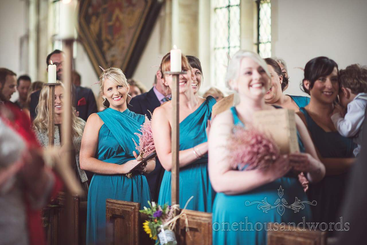 Smiling bridesmaids during church ceremony at Lulworth Castle Wedding Photographs