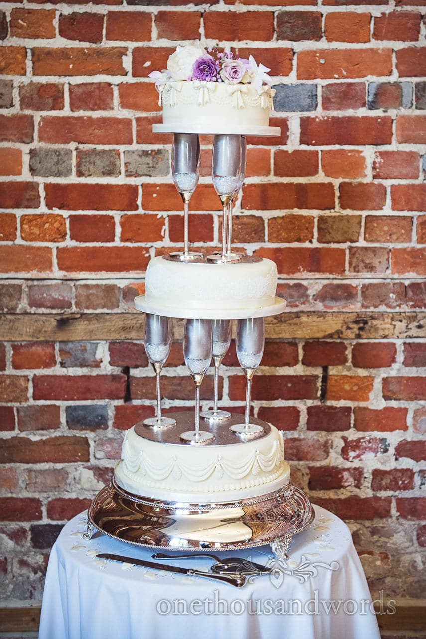 three tier champagne glass wedding cake against red brick wall at Highcliffe Castle