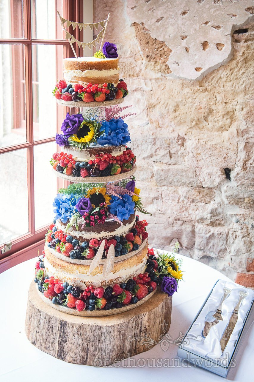 Towering wedding cake decorated with fruit and flowers from Lulworth Castle Wedding Photographs