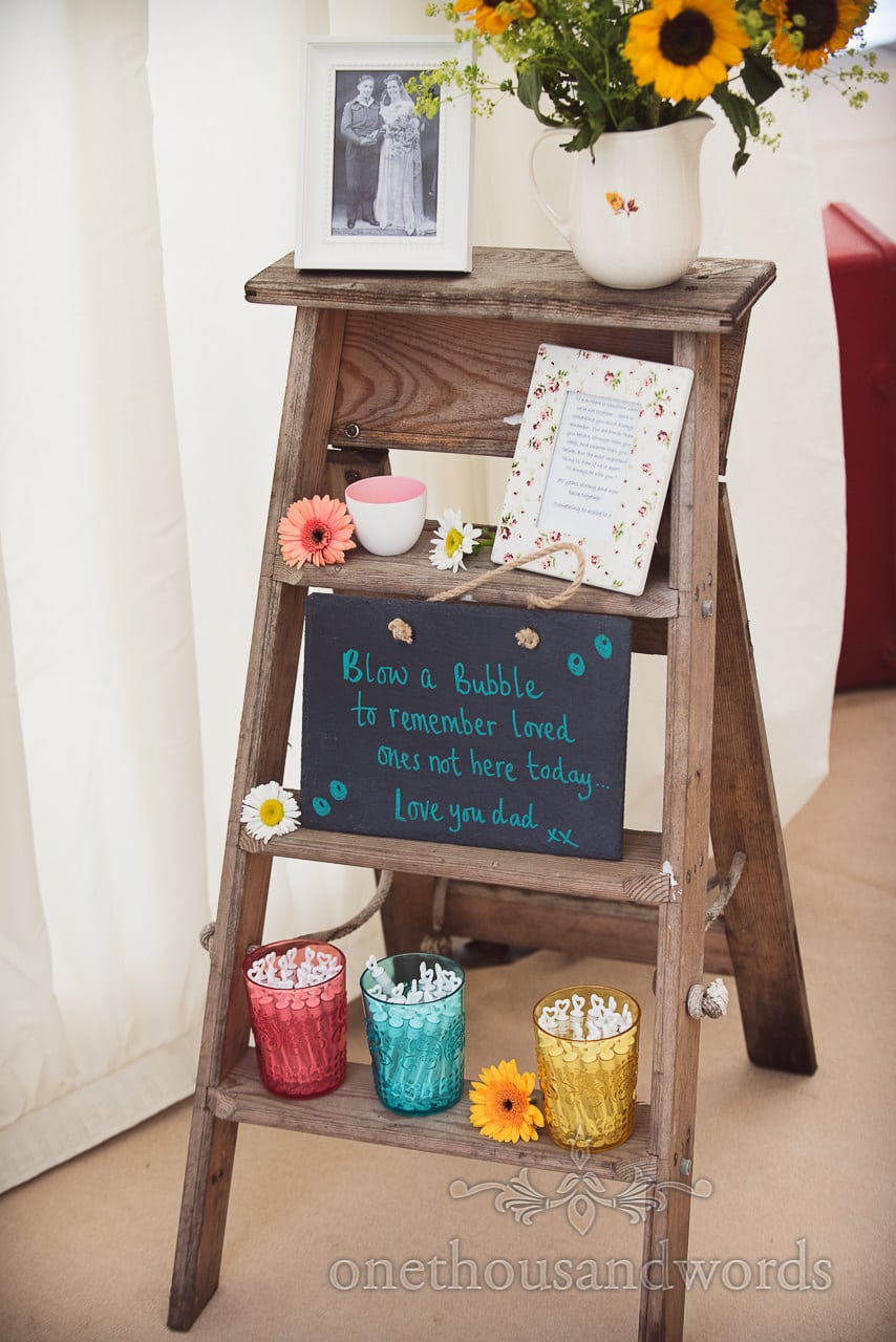 Wedding bubble wands in memory on wooden ladder at marquee wedding