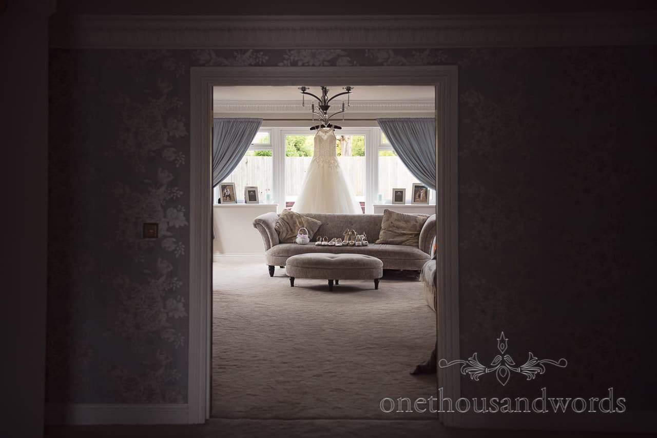 Wedding dress hangs in window with wedding shoes on sofa through doorway
