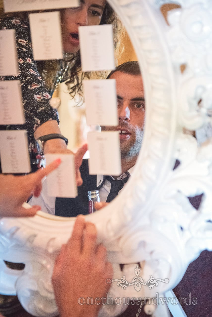 Wedding guests examine table plan mirror at Highcliffe Castle Wedding