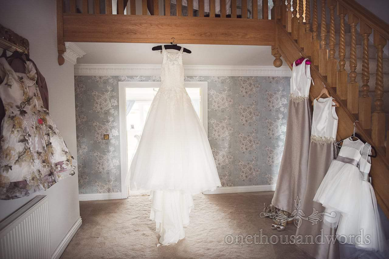 White wedding dress and bridesmaids dresses hang from stairs on wedding morning