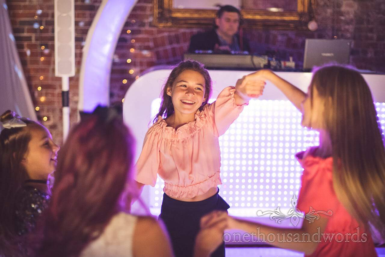 Young girl wedding guest dance in front of DJ at Highcliffe Castle Wedding