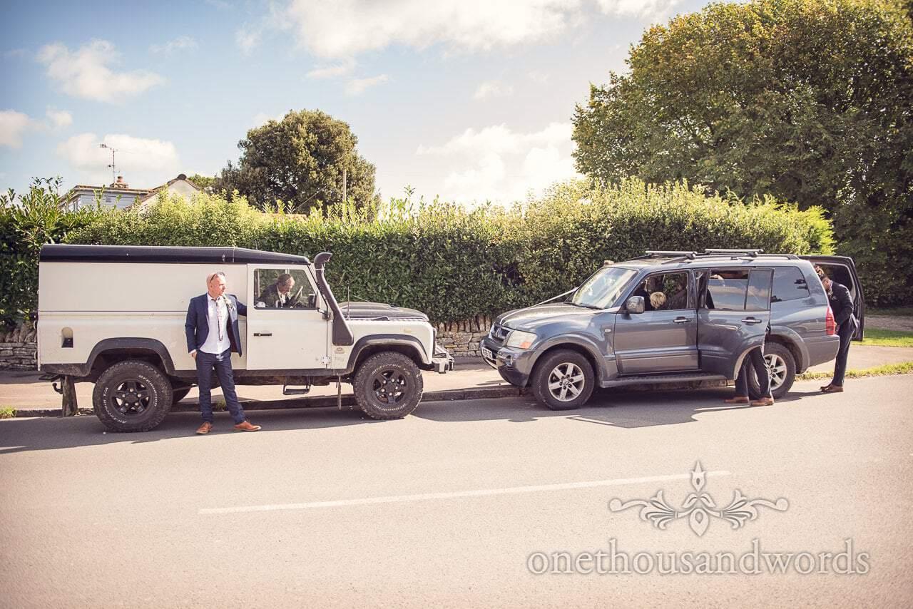 4 x 4 wedding cars ribboned by groomsmen on countryside wedding morning