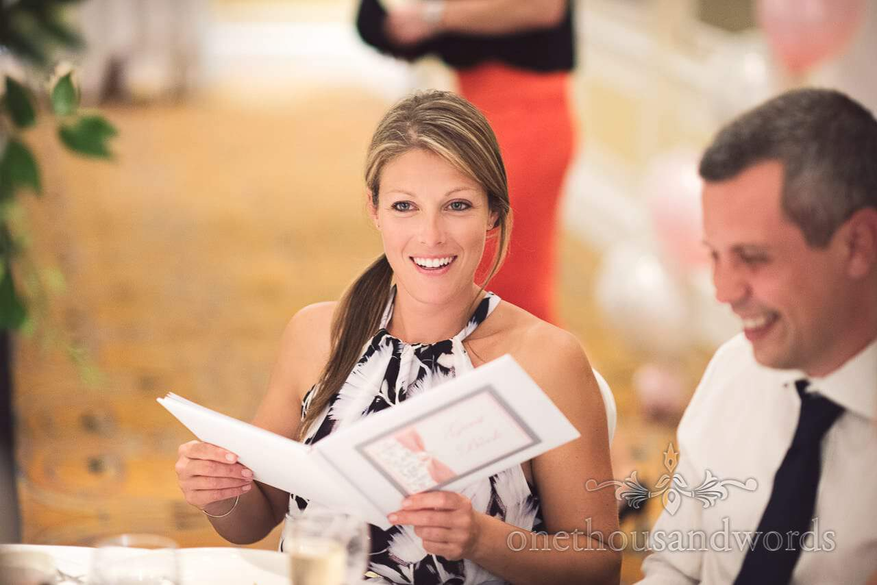 Beautiful guest reads wedding guest book during wedding breakfast at Bournemouth Marriott wedding venue