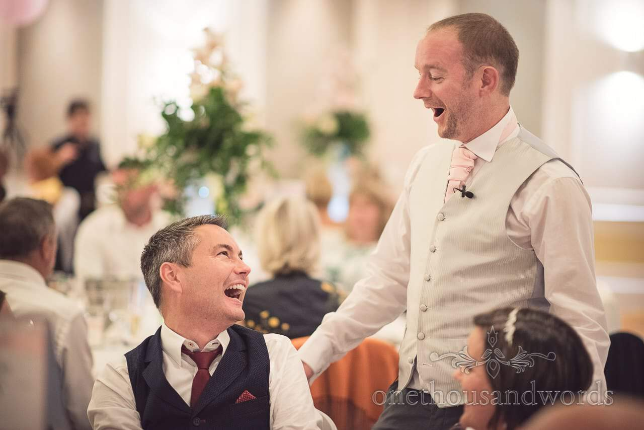 Best man and wedding guest laughing at jokes during wedding breakfast at Bournemouth Hotel