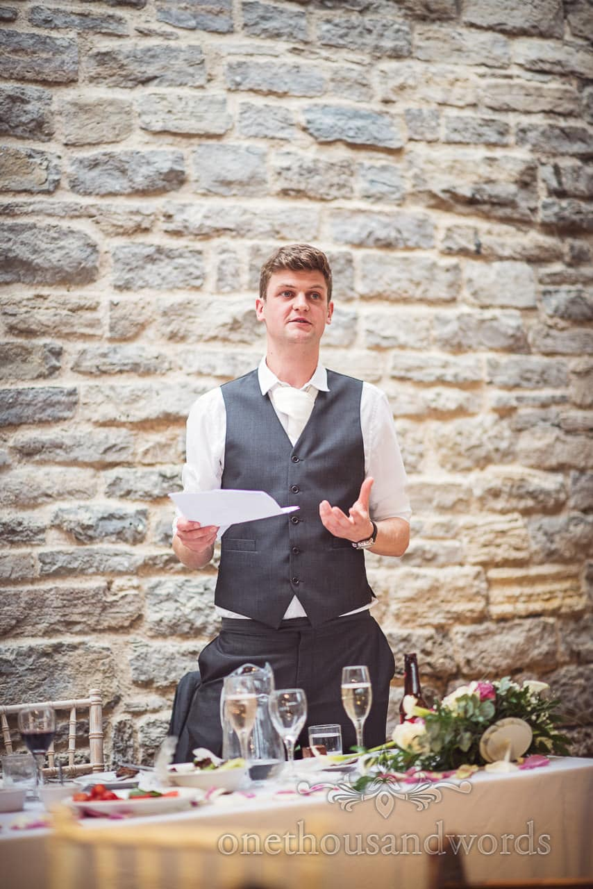Best man delivers speech against stone wall at Durlston Castle Wedding venue