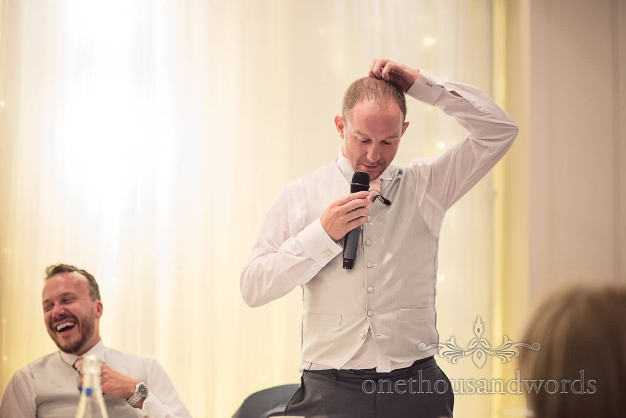 Best man in light grey waistcoat scratches his head as he makes wedding speech