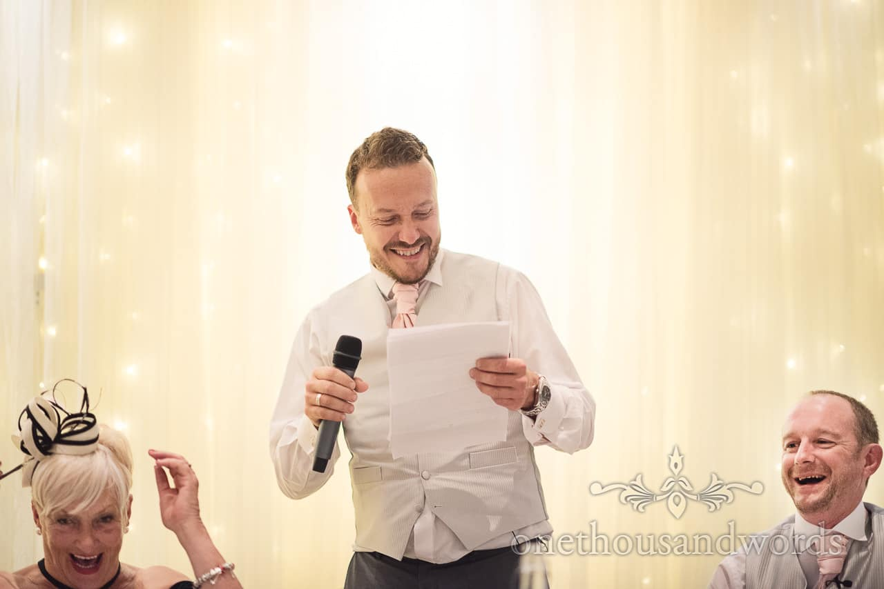 Best man tells joke during wedding speech against led curtain backdrop