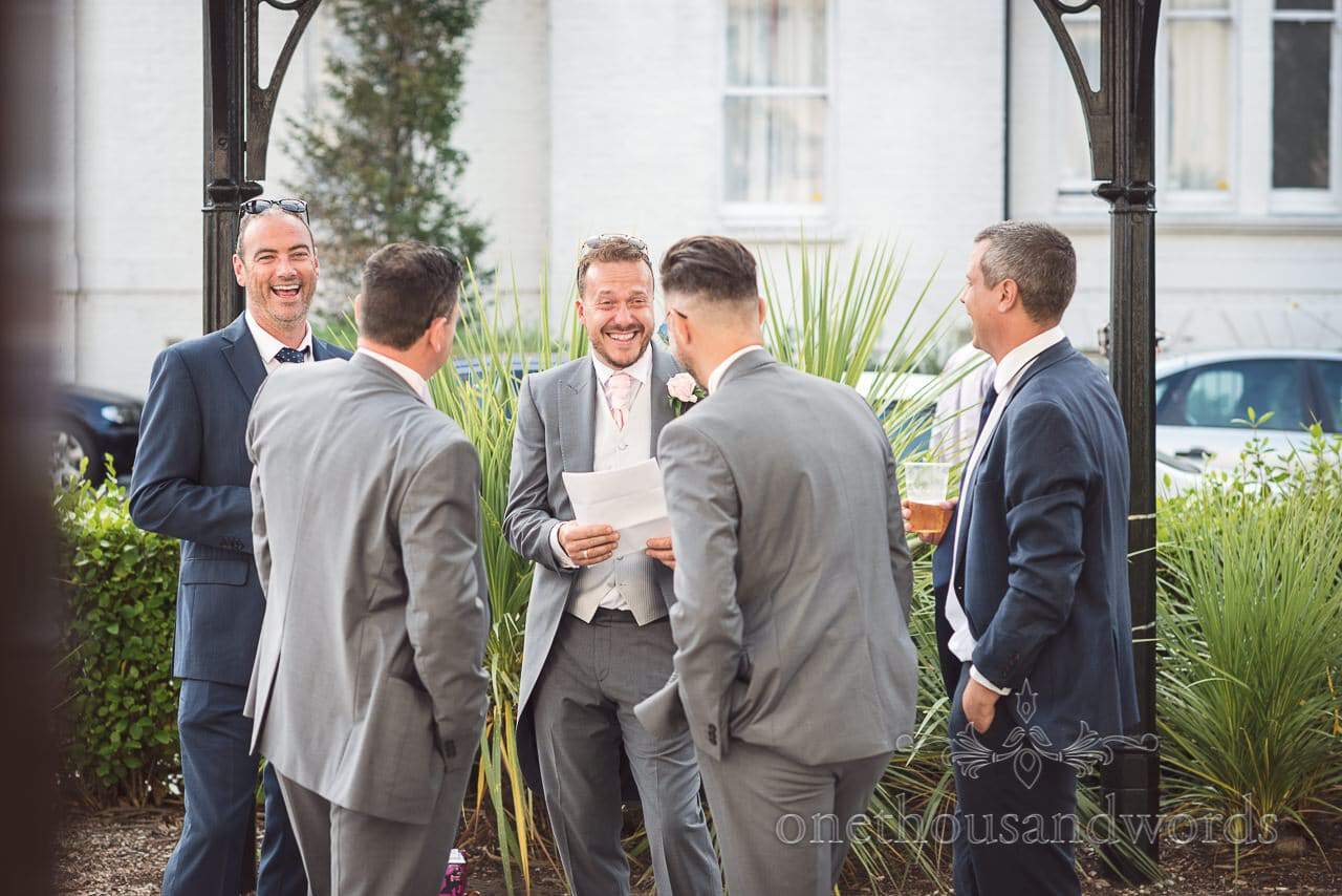 Best men in grey tail suits practice wedding speeches outside Bournemouth Highcliff Marriott Hotel