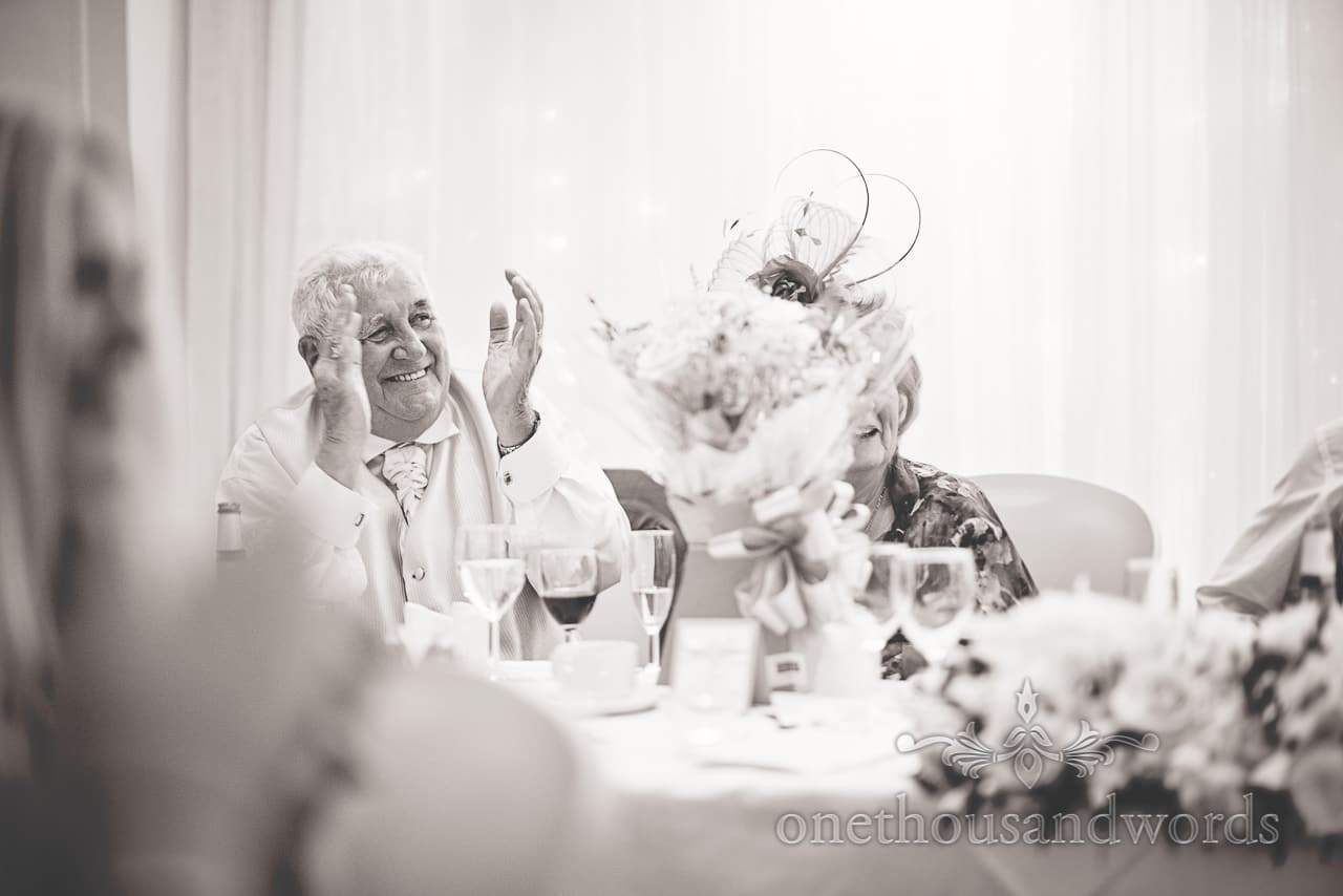 Black and white photo of Groom's father clapping during wedding speeches
