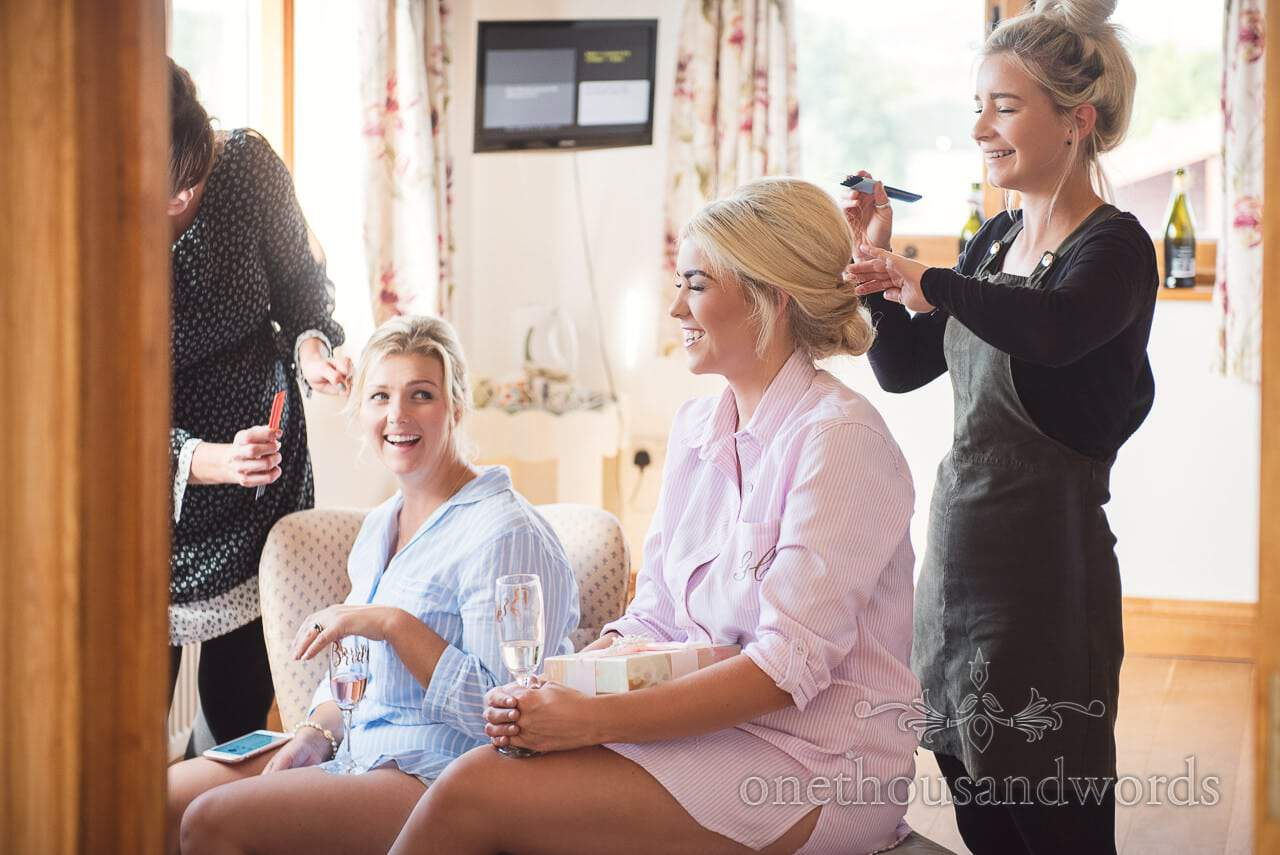 Bride and bridesmaid laughing as they have wedding hair styled during bridal preparations