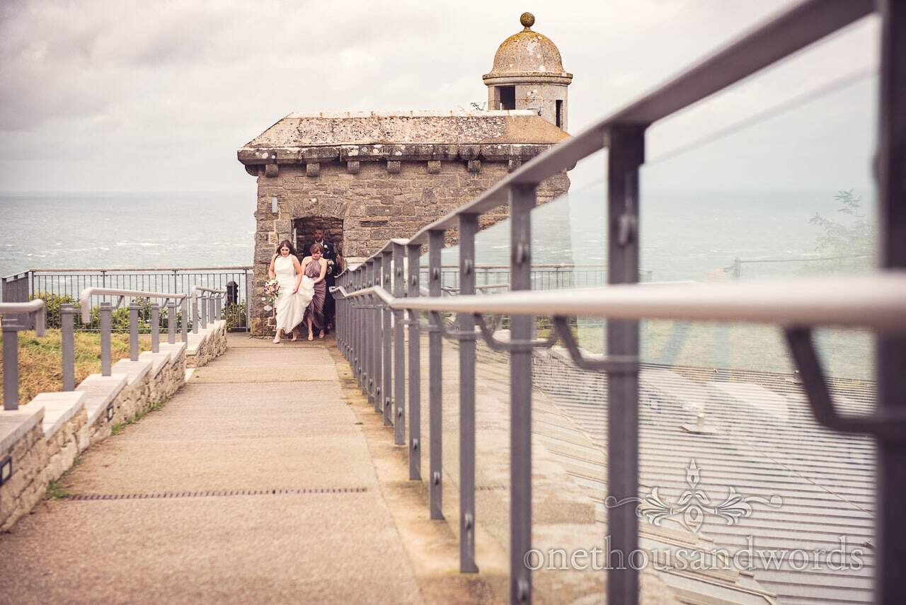 Bride and bridesmaids walk out of turret at Durlston Castle Wedding Photographs