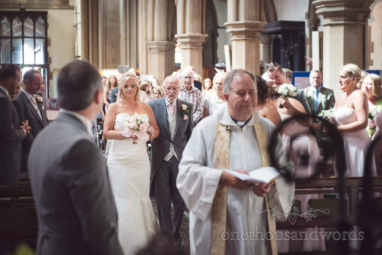 Bride and father walk up the aisle at St Peter's church wedding in Bournemouth