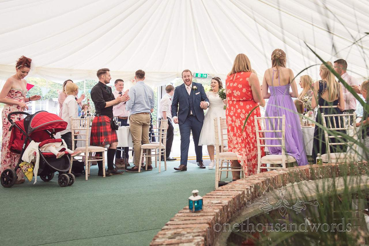 Bride and groom are welcomed into courtyard marquee at Coppleridge Inn Wedding Photographs
