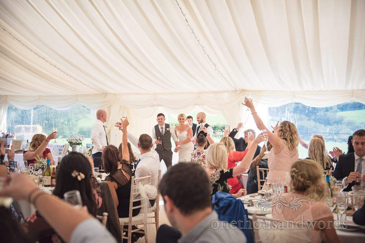 Bride and groom are welcomed into the marquee at Purbeck Valley Farm wedding photographs