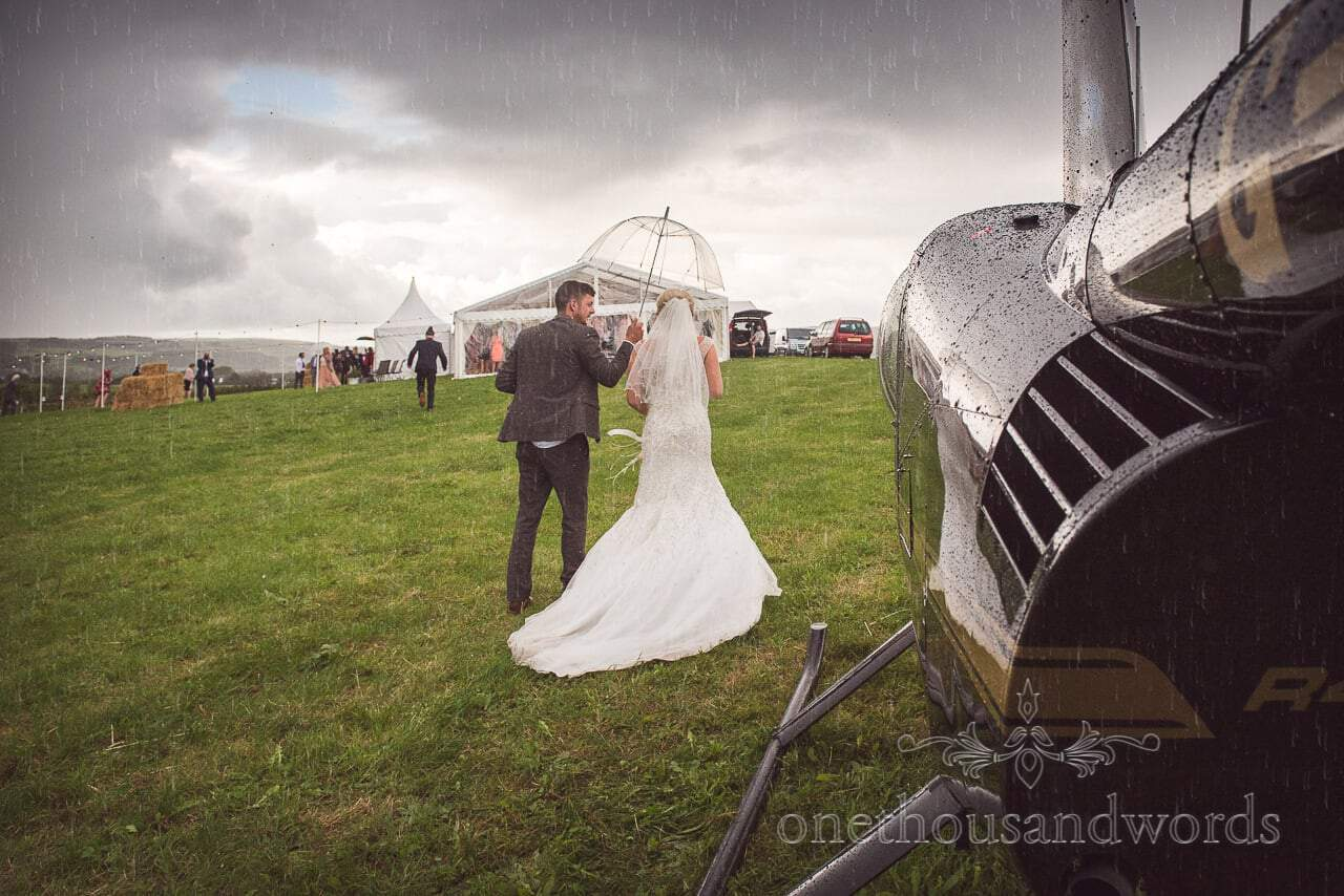 Bride and groom arrive by helicopter at Purbeck Valley Farm wedding photographs