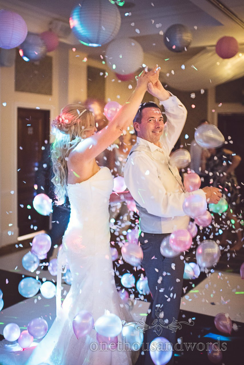 Bride and groom dance under balloon release confetti and balloons at Highcliffe Marriott