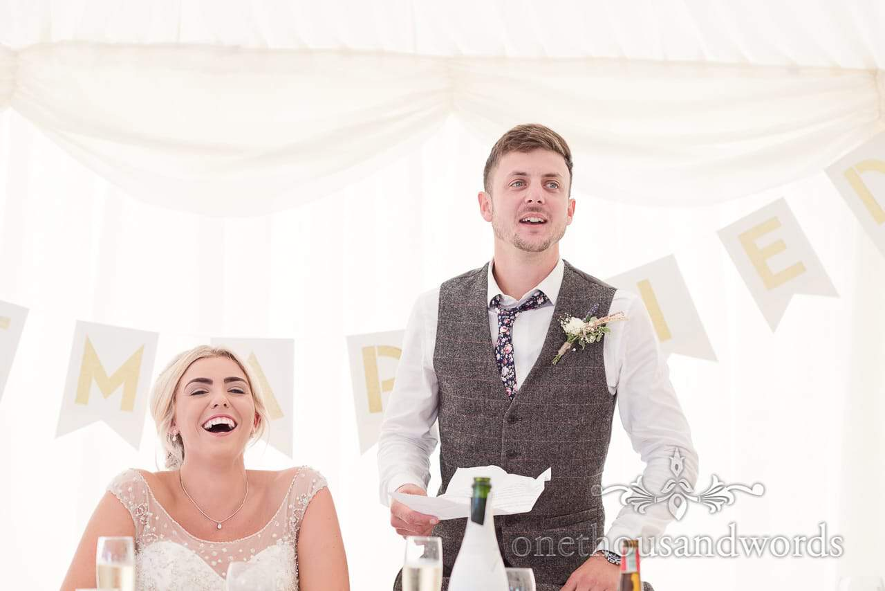 Bride and groom during grooms speech at Purbeck Valley Farm wedding photographs