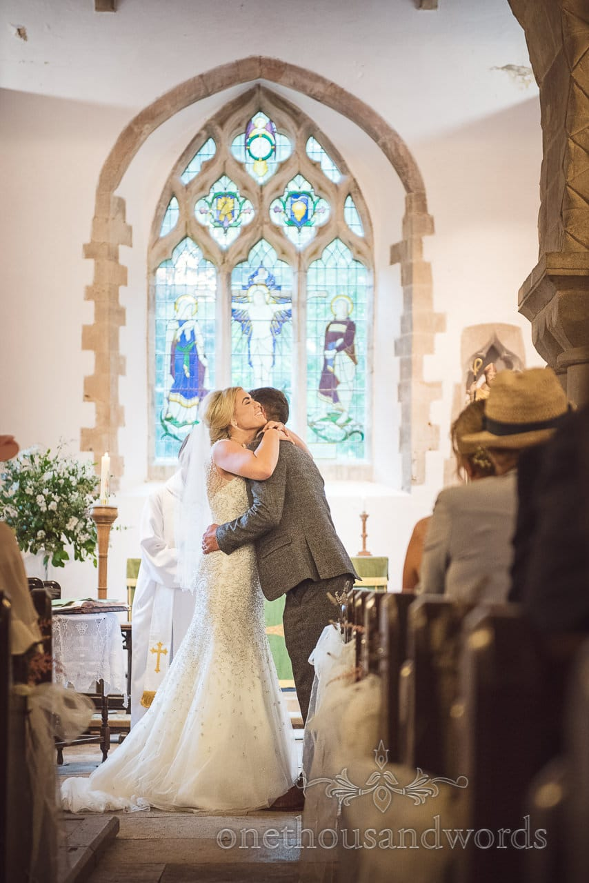 Bride and groom embrace in church from Purbeck Valley Farm wedding photographs