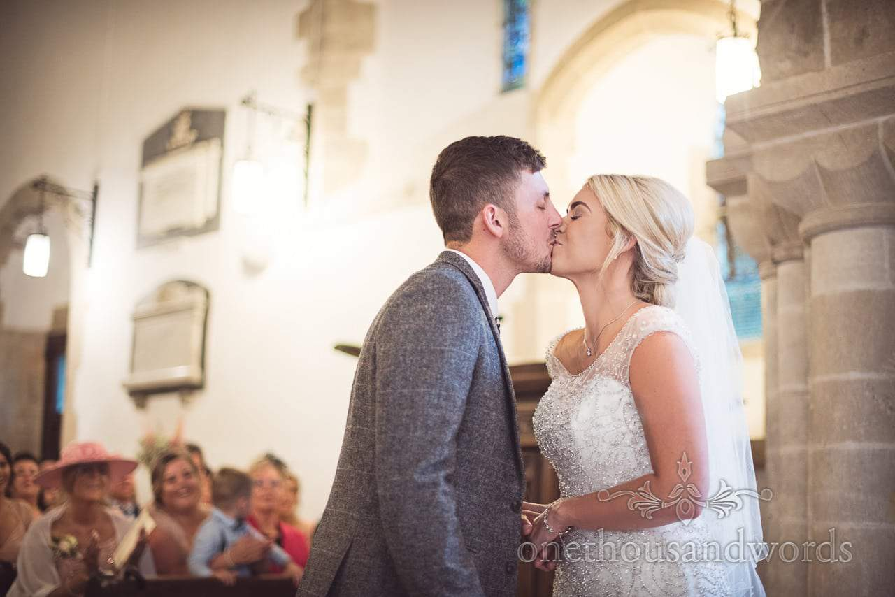 Bride and groom first kiss in English stone church wedding in Dorset