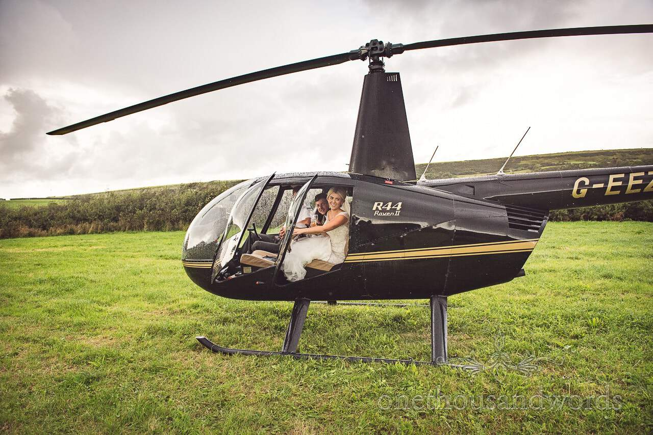 Bride and groom have champagne in helicopter before flying to reception venue