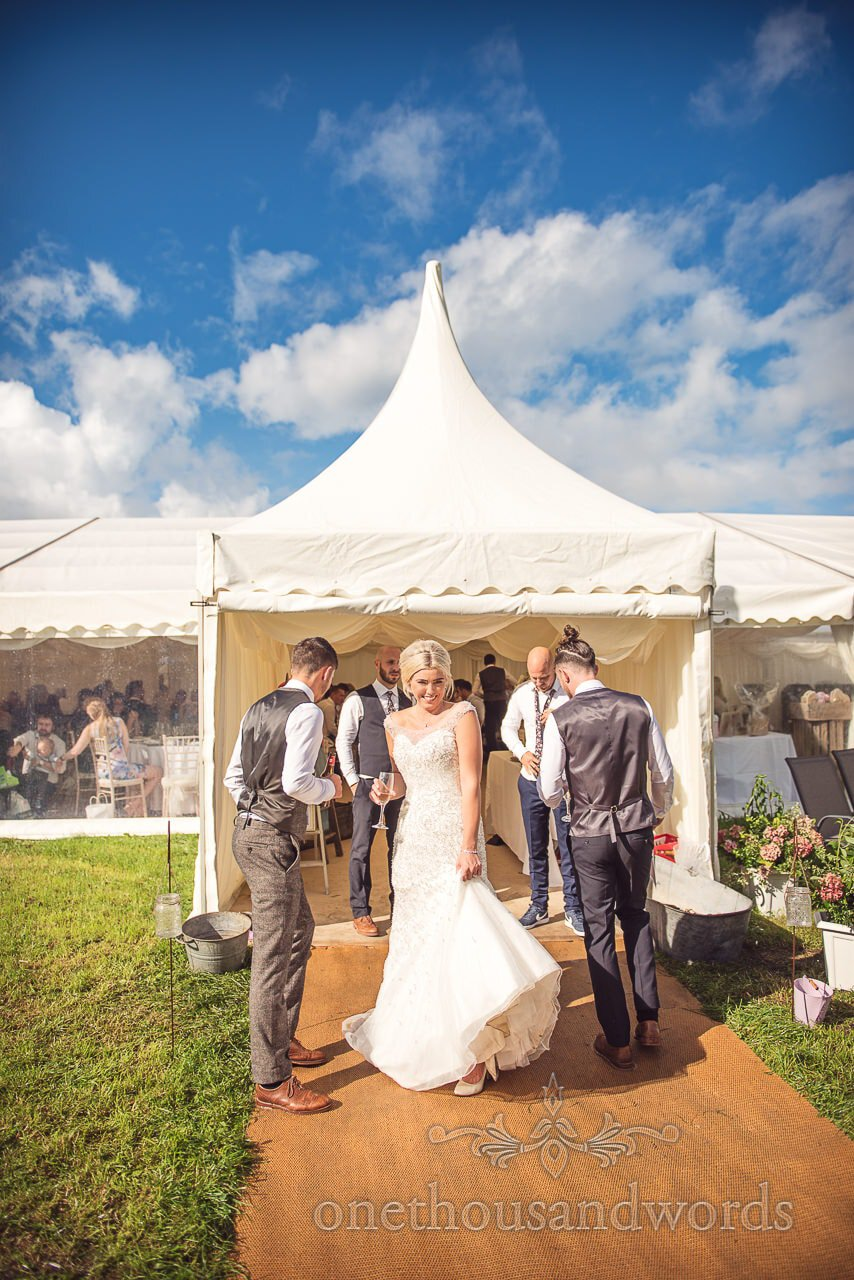 Bride and groom in sunshine outside marque at Purbeck Valley Farm wedding photographs