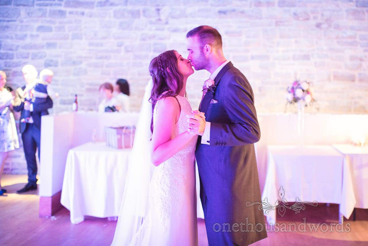 Bride and groom kiss during first dance at Durlston Castle Wedding Photographs