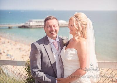 Bride and groom laughing portrait with Bournemouth Beach and Pier in background