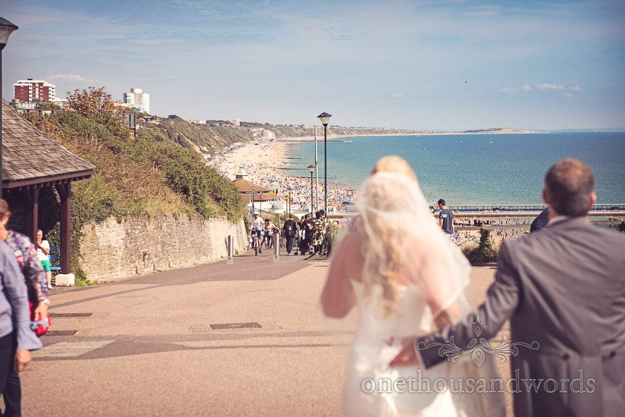 Bride and groom look at Bournemouth beach looking crowded on summers day