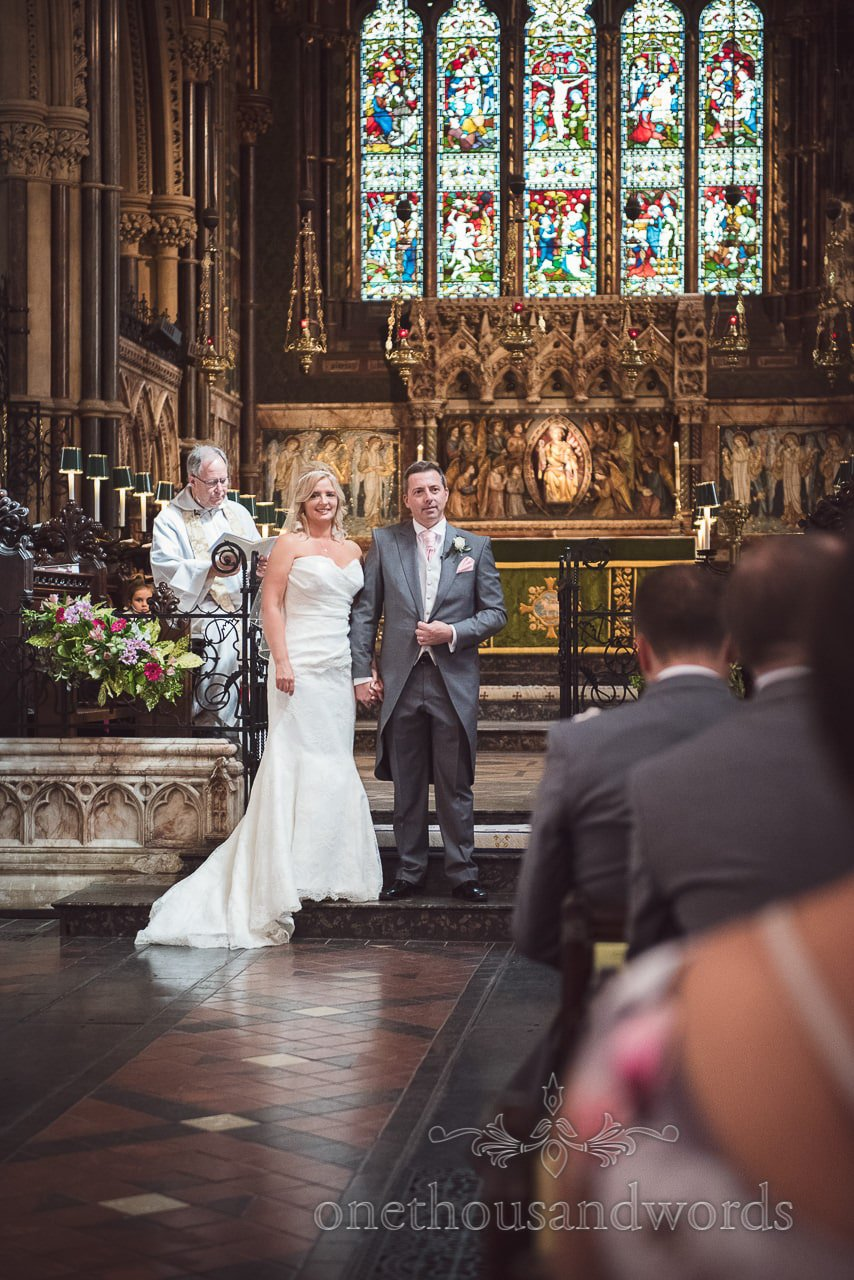 Bride and groom look over wedding ceremony congregation at St Peter's church in Bournemouth