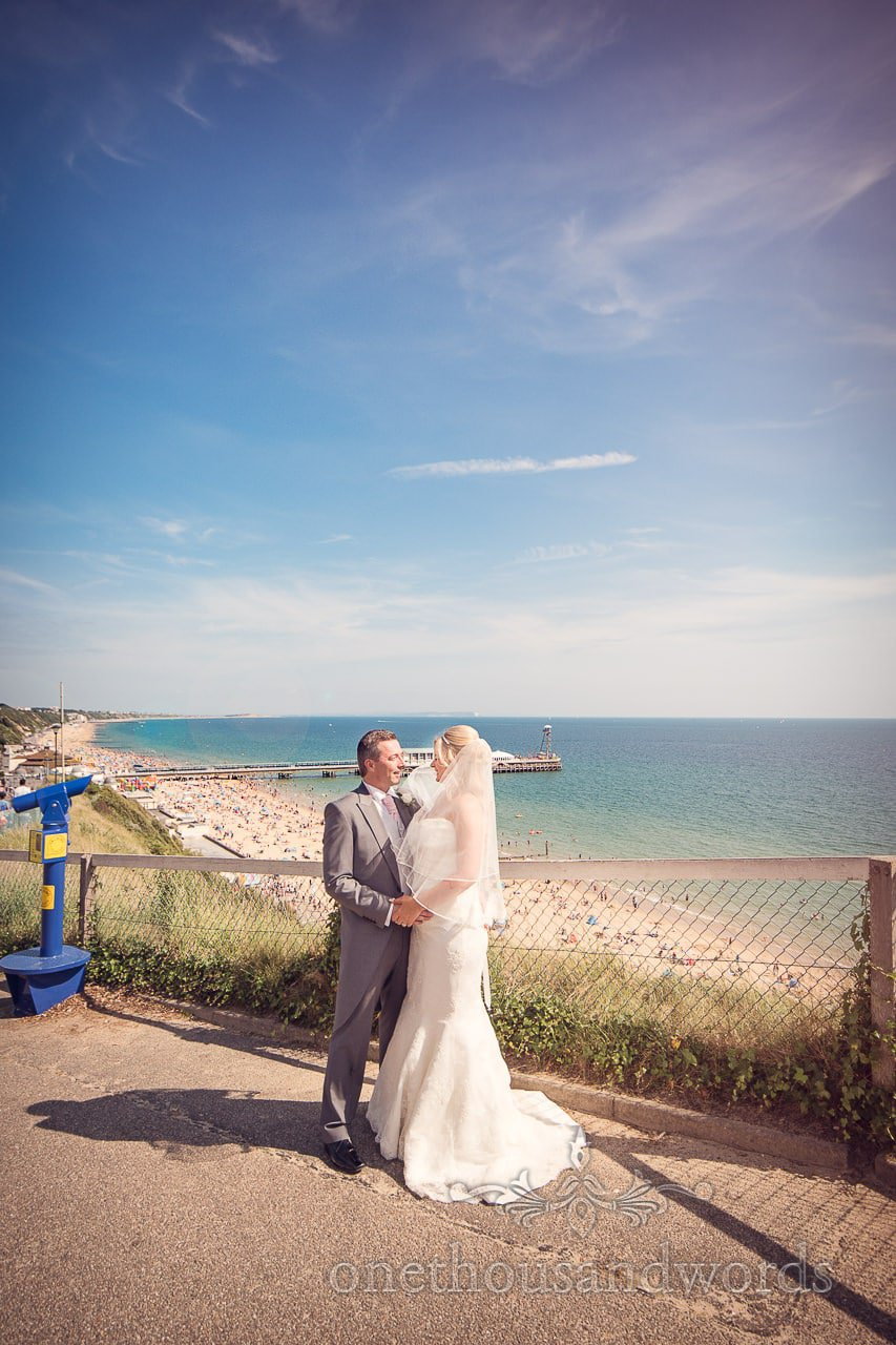 Bride and groom photograph overlooking Bournemouth beach and pier in Summer sun