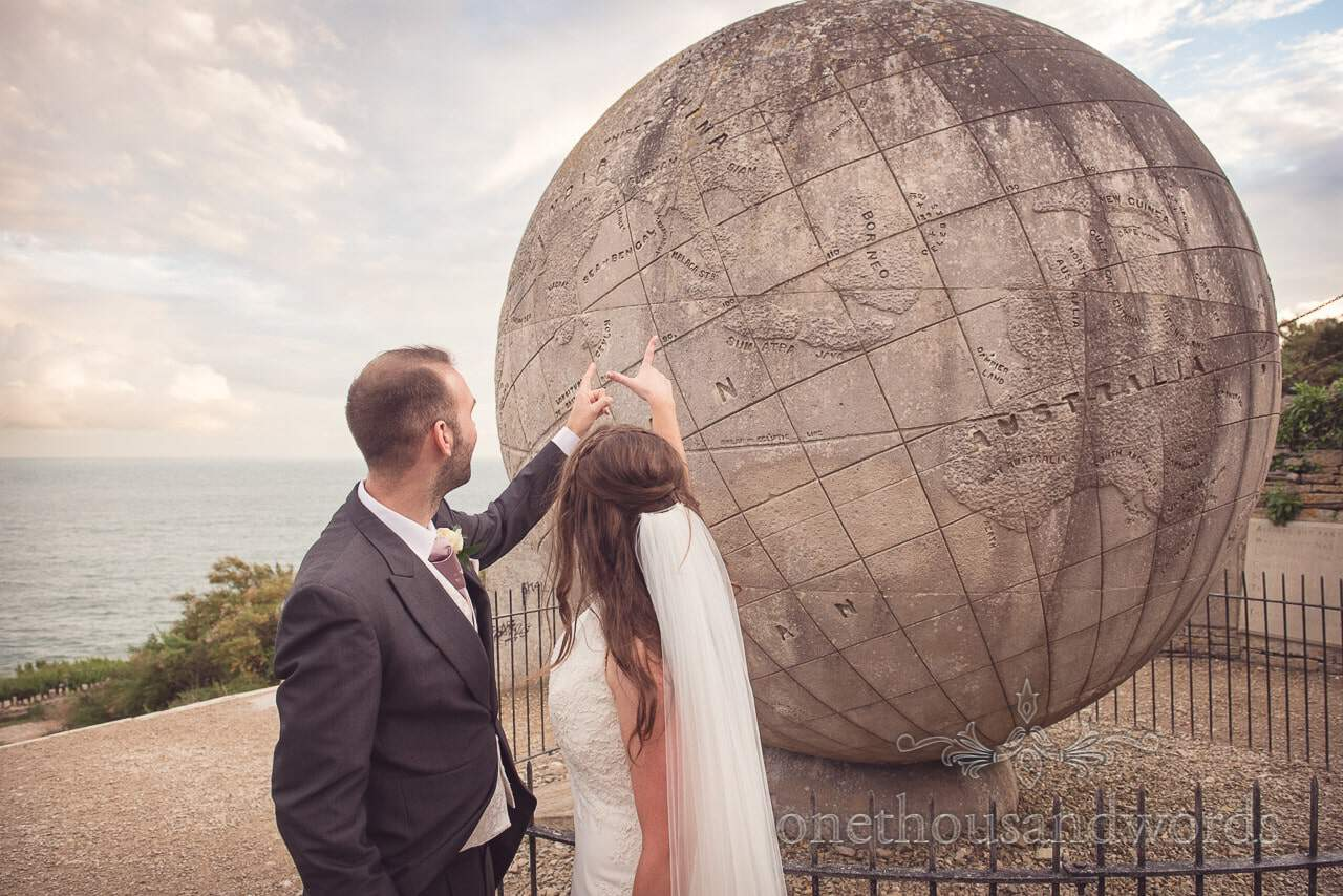 Bride and groom point to honeymoon destination on Durlston Castle Stone Globe