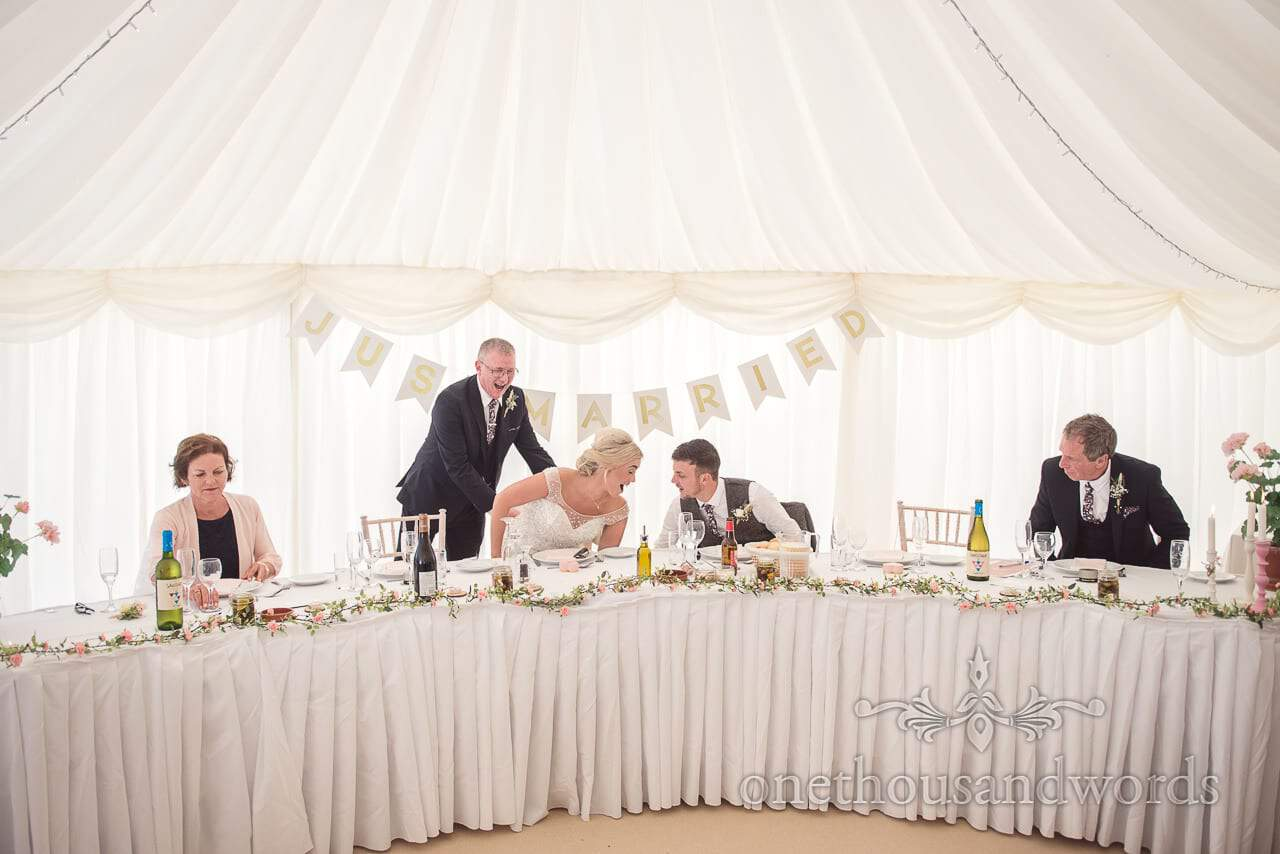 Bride and groom take their places for wedding breakfast at Purbeck Valley Farm wedding photographs