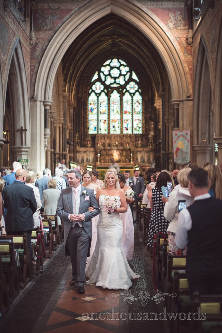 Bride and groom walk down the aisle at St Peter's Church in Bournemouth