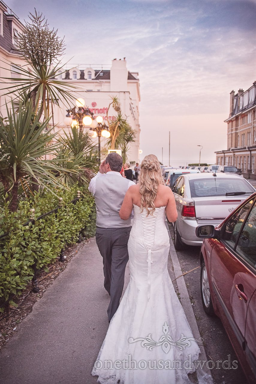 Bride and groom walk on pavement past Marriott hotel to Bournemouth Beach