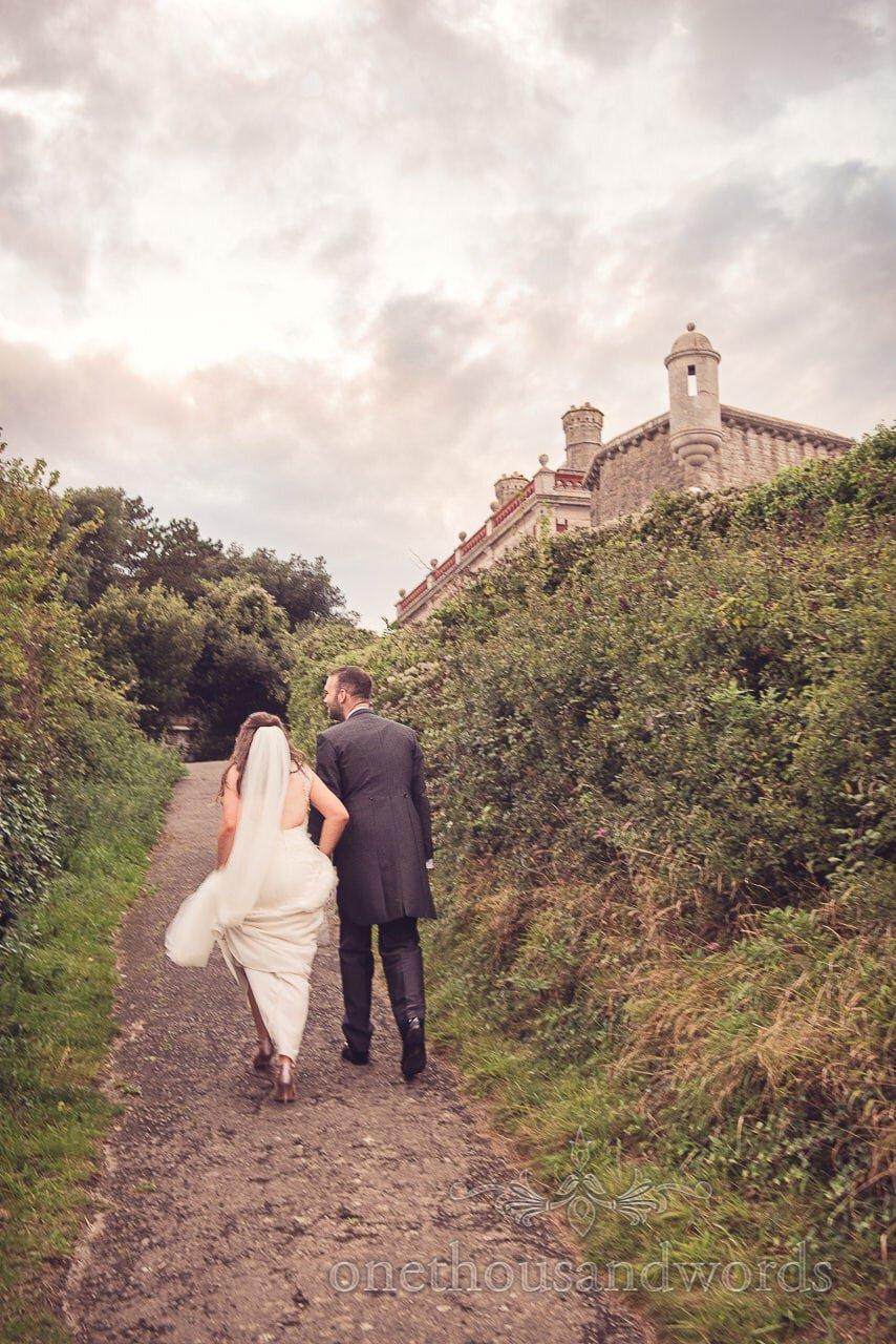 Bride and groom walk towards Durlston Castle Wedding Venue