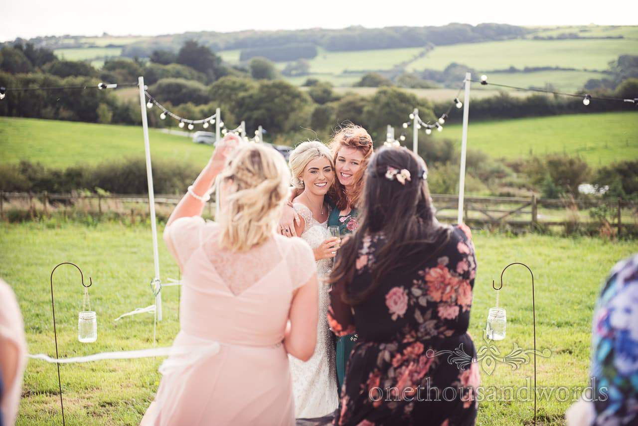 Bride and guests outside the marquee at Purbeck Valley Farm wedding photographs