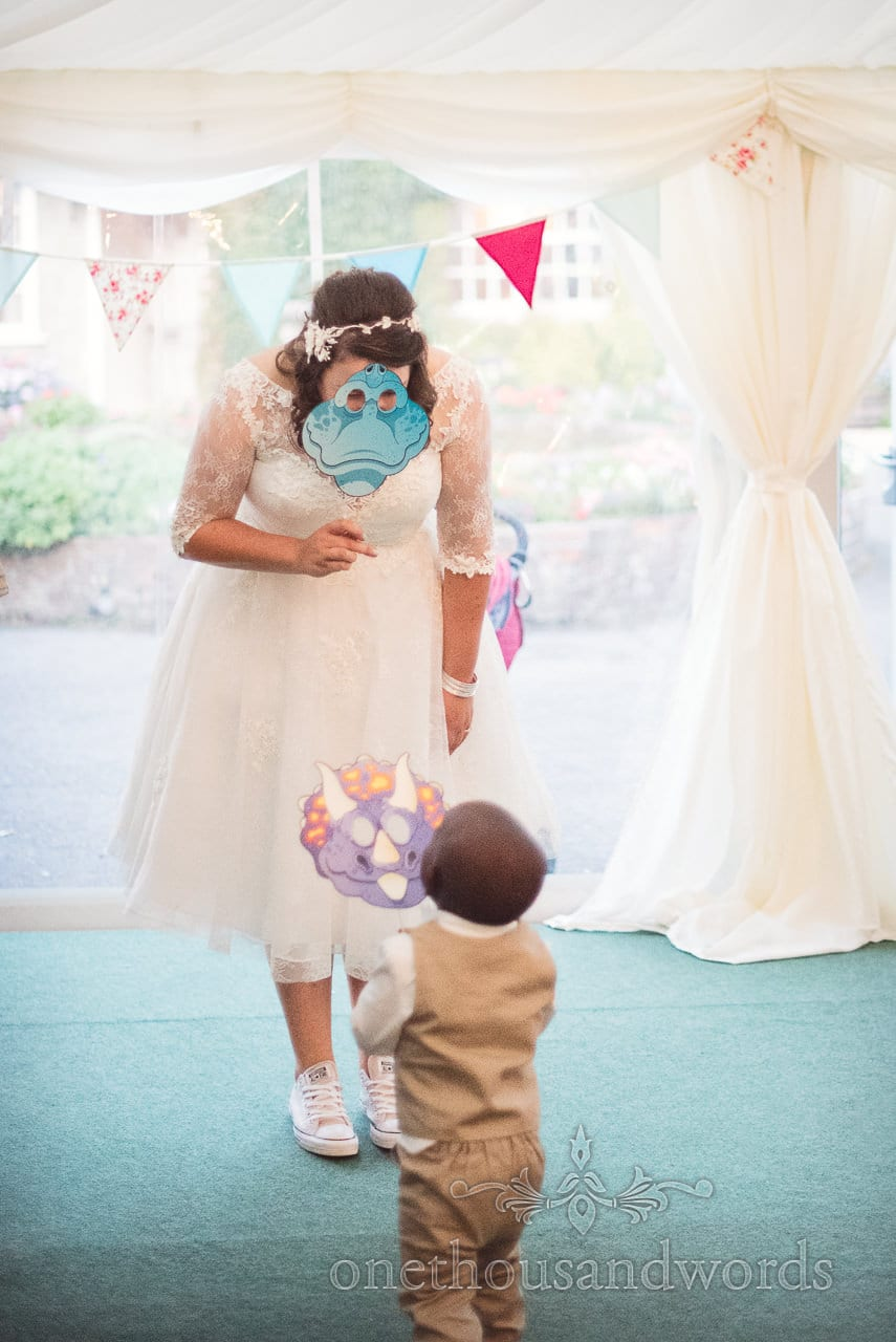 Bride and young guest play with masks at Coppleridge Inn Wedding Photographs