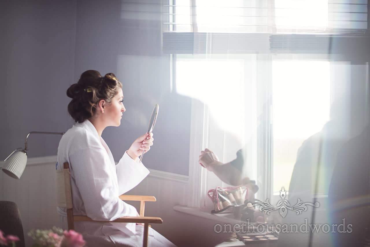 Bride checks wedding make-up in hand mirror next to window on wedding morning