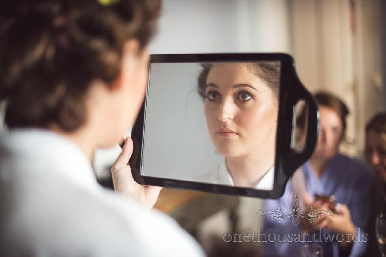 Bride checks wedding make-up in mirror during bridal preparations in Dorset