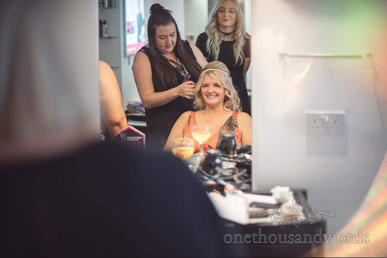 Bride has hair styled in hairdressers mirror on wedding morning preparations