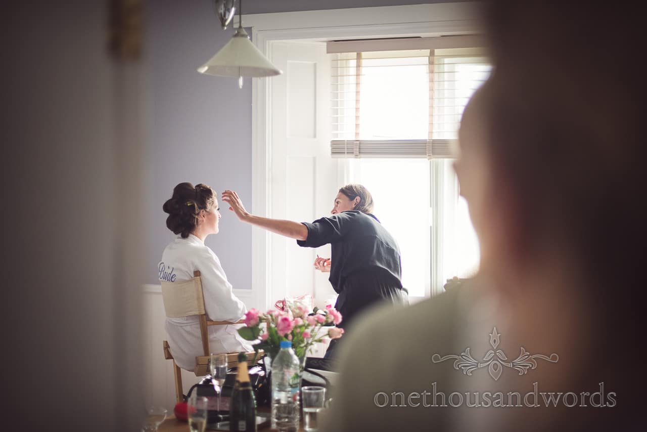 Bride has wedding make up styled during bridal preparations in Dorset