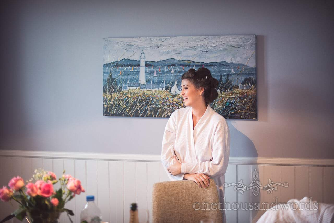 Bride in dressing gown laughing during wedding morning preparations