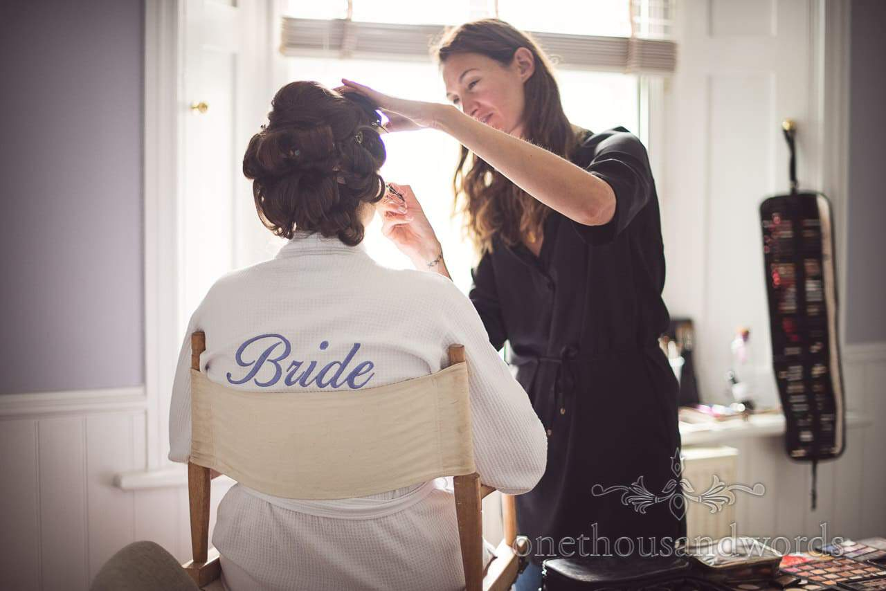 Bride in dressing gown with bride scrip on back has wedding make up styled